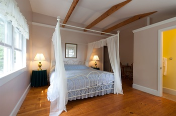white canopy bed and the wood floor
