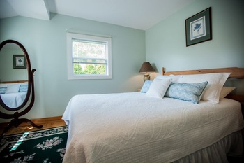 QUEEN BED WITH PILLOWS AND SMALL WINDOW