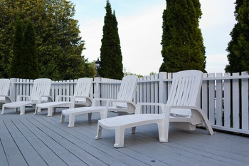white lounging chairs sitting on the porch